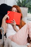 Young Woman Sitting on Chair While Reading a Book. Pretty Young Woman Sitting on a Chair Beside her Bed with Legs Crossed, While Reading a Red Book Seriously Stock Image