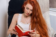 Young Woman Sitting on Chair While Reading a Book Royalty Free Stock Photo