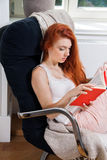 Young Woman Sitting on Chair While Reading a Book Royalty Free Stock Photography