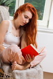 Young Woman Sitting on Chair While Reading a Book Stock Images