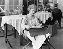 Young woman sitting on a chair and reading documents. (All persons depicted are no longer living and no estate exists. Supplier grants that there will be no Stock Image