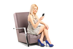 A young woman sitting on a chair and talking on a mobile phone Stock Images