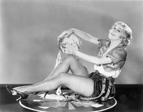 Young woman sitting on a circle playing a tambourine Stock Image