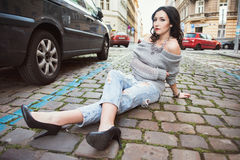 Young woman sitting on the city street Royalty Free Stock Images