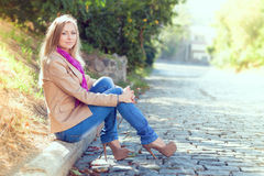 Young woman sitting, cityscape. Portrait of a beautiful young woman. Woman sitting on the parapet. profile view. Cityscape Royalty Free Stock Image
