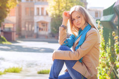 Young woman sitting, cityscape. Portrait of a beautiful young woman. Woman sitting on the parapet. profile view. Cityscape Stock Photos