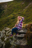 Young woman sitting on a cliff and enjoying a view Stock Photos
