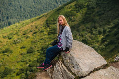 Young woman sitting on a cliff and enjoying a view Stock Images
