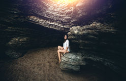 Young woman sitting on cliff at grotto at sunset rays Royalty Free Stock Photography