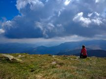 Young woman sitting on a cliff looking at mountains view and blue cloudy sky. Young girl dreaming about traveling royalty free stock image