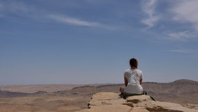 Young woman sitting on cliff`s edge and looking at the desert stock video footage