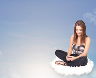 Young woman sitting on cloud with copy space Royalty Free Stock Photo
