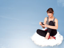 Young woman sitting on cloud with copy space Stock Photo