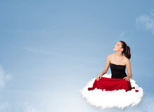Young woman sitting on cloud with copy space Royalty Free Stock Images