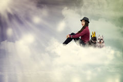 Young woman sitting on the cloud with dogs Stock Photos