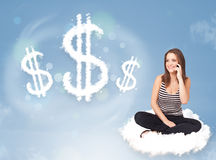 Young woman sitting on cloud next to cloud dollar signs Stock Photo