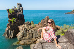 Young woman sitting on coastal rocks of Koh Chang. Island in Thailand Stock Photos
