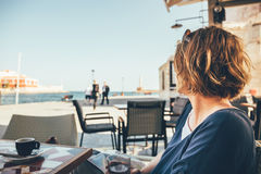 Young woman sitting in coffee bar and looking at old port in Chania Stock Images