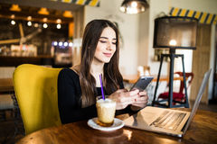Young woman sitting in coffee shop at wooden table, drinking coffee and using smartphone. On table is laptop. Girl browsing intern Stock Image