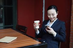 Young woman sitting in coffee shop at wooden table, drinking coffee and using smartphone.On table is laptop Royalty Free Stock Photo