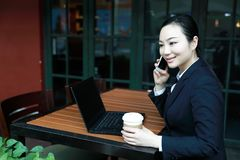 Young woman sitting in coffee shop at wooden table, drinking coffee and using smartphone.On table is laptop Stock Photos