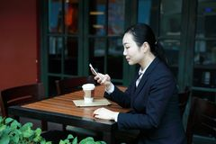 Young woman sitting in coffee shop at wooden table, drinking coffee and using smartphone.On table is laptop royalty free stock photos