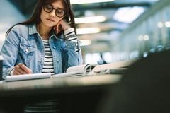 Young woman sitting at college library and studying. Girl writing notes at college campus royalty free stock image