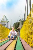 Young woman sitting on a colorful wooden bridge. Bali island. royalty free stock photography
