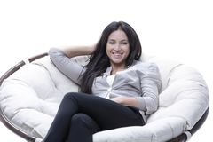 Young woman sitting in a comfortable soft big armchair. Tired woman sitting in a cozy comfortable armchair. photo with copy space Royalty Free Stock Photos