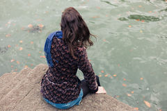 Young woman sitting on concrete pier Stock Image