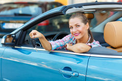 Young  woman sitting in a convertible car with the keys in hand Stock Photos