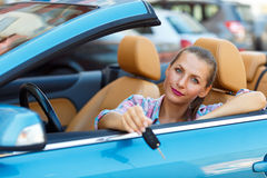 Young  woman sitting in a convertible car with the keys in hand Royalty Free Stock Images