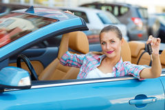 Young  woman sitting in a convertible car with the keys in hand Royalty Free Stock Photo