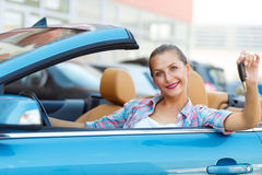 Young  woman sitting in a convertible car with the keys in hand Stock Image
