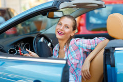 Young  woman sitting in a convertible car with the keys in hand Stock Photography