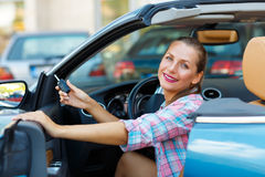 Young  woman sitting in a convertible car with the keys in hand Stock Images
