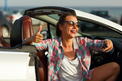 Young woman sitting in a convertible car with the keys in hand. Young pretty woman sitting in a convertible car with the keys in hand - concept of buying a used Stock Photo