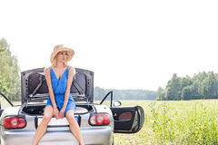 Young woman sitting on convertible trunk against clear sky Royalty Free Stock Photos