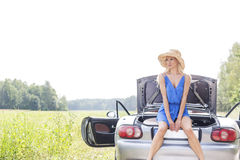 Young woman sitting on convertible trunk against clear sky Stock Image