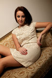 Young woman sitting on the couch Stock Images
