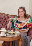 Young woman sitting on a couch and drinking tea Stock Photos
