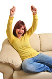 Young woman sitting on a couch and is  happy Stock Photography