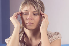 Young woman sitting on a couch, holding her head, having a strong headache royalty free stock photos