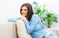Young woman sitting on couch. Royalty Free Stock Photos