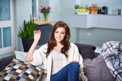Young woman sitting on couch Stock Photography