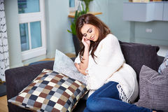 Young woman sitting on couch Stock Photos