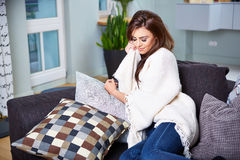 Young woman sitting on couch Stock Images