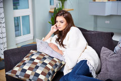 Young woman sitting on couch Royalty Free Stock Image