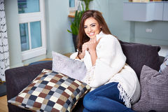 Young woman sitting on couch Royalty Free Stock Photography