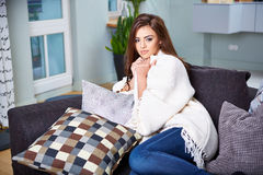 Young woman sitting on couch Stock Photo